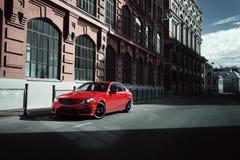 Czerwony samochodu pobyt na asfaltowej drodze w mieście przy dniem zdjęcia royalty free