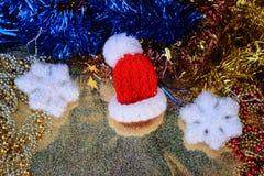 Czerwony Santa kapelusz w miniaturowym zakończeniu up na błyszczącym złocistym tle z świątecznymi dekoracjami Zdjęcia Stock