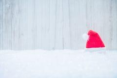 Czerwony Santa kapelusz w śniegu Zdjęcia Stock