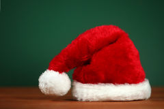 Czerwony Santa kapelusz Z kopii przestrzenią na Zielonym i Drewnianym tle Zdjęcie Royalty Free