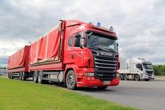 Czerwony Scania, Zielona trawa, Popielaty niebo Obrazy Stock