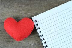 Czerwony serca i pustego miejsca notatnik umieszczający na drewnianej podłoga Obraz Royalty Free