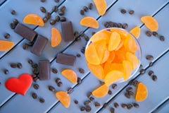 Czerwony serce, czekolady i pomarańczowy marmoladowy w round zlewki szklanym kłamstwie na stole malować drewniane deski, obraz royalty free