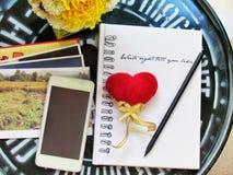 Czerwony serce i ołówek na notatniku, telefon komórkowy, fotografie ja robi pocztówce i kwiaty na zielonym stal stole robią mu yo Obraz Royalty Free