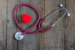 Czerwony serce i stetoskop na starym drewnianym biurku horyzontalny fotografia royalty free