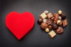 Czerwony serce kształtował pudełko z czekoladowymi pralines na ciemnym tle Fotografia Stock
