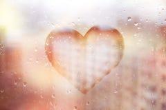 Czerwony serce malujący na szkła mokrym okno w mieście obraz stock