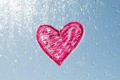 Czerwony serce malujący z pomadką na okno z wodnymi kroplami Tła błękitny pogodny niebo, krople błyszczy w słońcu zdjęcie royalty free