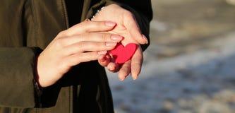 Czerwony serce w żeńskich rękach z piękną menchią robi manikiur zdjęcia stock