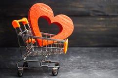 Czerwony serce w supermarketa tramwaju pojęcie kupienie miłość to walentynki dni Żółty tło Miłość zakupy Ulubiony stora fotografia stock