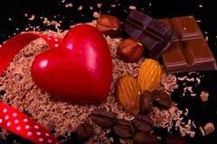 Czerwony serce z zmrokiem i dojna czekolada, kawa, dokrętki na czerni obrazy stock