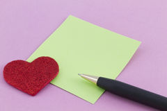 Czerwony serce, zieleni notatka i pióro na różowym tle, Fotografia Royalty Free