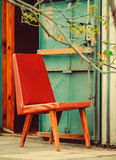 Czerwony skóry namiastki krzesło obok Stalowego drzwi, kraj chałupy wakacje, wakacje, kraj wioska, Tonująca Obrazy Royalty Free