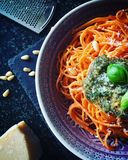 Czerwony spaghetti makaron z zielonym świeżym pesto kumberlandem, basilów liśćmi, sosnowymi dokrętkami i serem, Zdjęcia Royalty Free