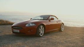 Czerwony sportowy samochód na wybrzeżu ocean zbiory