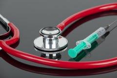 Czerwony stetoskop i zielona hypodermic igła na lab worktop Zdjęcie Royalty Free