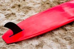 Czerwony surfboard na piasku Zdjęcia Royalty Free