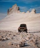 Czerwony SUV w pustyni przeciw tłu jar zdjęcia stock