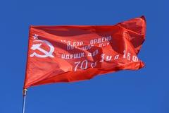 Czerwony sztandar przeciw pięknemu niebu Obrazy Royalty Free