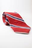 Czerwony szyja krawat z błękitnych i bielu lampasami kłaść na białym tle Fotografia Stock