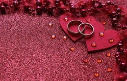 Czerwony tło z dwa pierścionkami i kierowym, blisko małych szklanych serc i koralików z faborkiem obraz royalty free