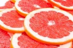 Czerwony tło grapefruitowi plasterki Obrazy Stock