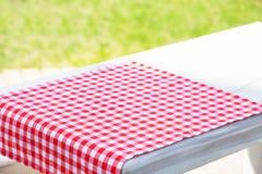 Czerwony tablecloth w klatce na stole Zdjęcia Stock