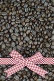 Czerwony tartanu faborek na kawowych fasoli tle Zdjęcie Royalty Free