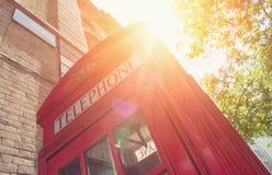 Czerwony Telefoniczny budka z słońcem przy latem w Londyńskiej ulicie zdjęcie royalty free
