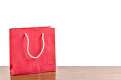 Czerwony torba na zakupy na drewnianym stole Obrazy Royalty Free