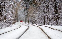 Czerwony tramwaj jedzie przez zima lasu między drzewami zakrywającymi z białym śniegiem zdjęcia stock