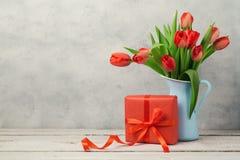 Czerwony tulipan kwitnie bukieta i prezenta pudełko nad nieociosanym tłem Kobiety dzień lub urodziny świętowanie Zdjęcia Royalty Free