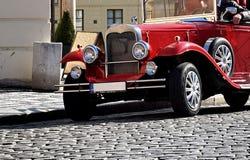 Czerwony turystyczny oldtimer od początku xx wiek na historycznej brukującej drodze w Praga Fotografia Royalty Free
