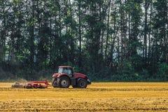 Czerwony uprawia ziemię ciągnik pracuje w polu Dysk brona dla miażdżących stubbles Obraz Stock