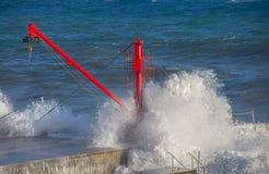 Czerwony żuraw na molu z szorstkim morzem fotografia stock