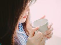 Czerwony usta azjatykcia dziewczyna w błękitnego flanelowego koszulowego chwyta gorącej kawie fo Zdjęcie Royalty Free