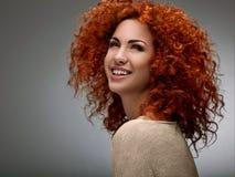 Czerwony włosy. Piękna kobieta z Kędzierzawym włosy. Wysokiej jakości wizerunek. Fotografia Stock