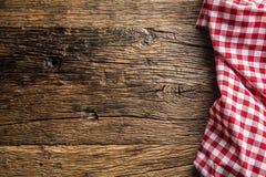 Czerwony w kratkę kuchenny tablecloth na nieociosanym drewnianym stole obrazy stock