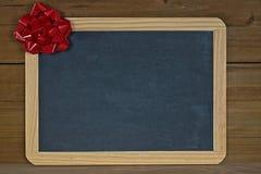 Czerwony wakacyjny łęk na chalkboard obrazy royalty free