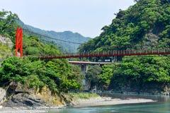 Czerwony wiszący most lub zawieszenie most nad zielona rzeka w dolinie obraz royalty free