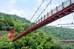 Czerwony wisz?cy most lub zawieszenie most w dolinie zdjęcia stock