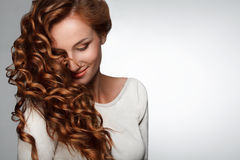 Czerwony włosy. Kobieta z Pięknym Kędzierzawym włosy Obrazy Stock