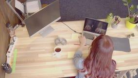 Czerwony z włosami freelance żeński działanie z podołka wierzchołkiem, opowiada na telefonie zbiory