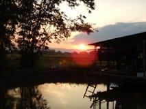 Czerwony zmierzch odbija z drewnianego spławowego jezioro domu Zdjęcie Stock