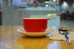 Czerwony zupny puchar z łyżką -, miejsce na stole Fotografia Stock