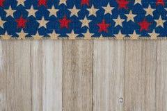 Czerwonych i błękitnych gwiazd burlap faborek na wietrzejącym drewnianym tle Obrazy Royalty Free