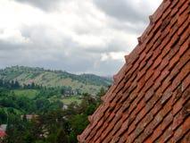 Czerwonych płytek dach, chmury i zieleń krajobraz na tle, Zdjęcia Royalty Free