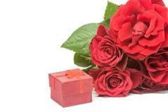 Czerwonych róż bukiet i mały ślubny pierścionek zaręczynowy boksujemy na biel przestrzeni propozyci pojęciu Fotografia Royalty Free