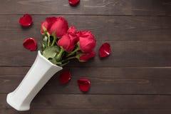 Czerwonych róż kwiat jest w białej wazie na drewnianym tle Zdjęcia Royalty Free