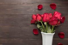 Czerwonych róż kwiat jest w białej wazie na drewnianym tle Obrazy Stock